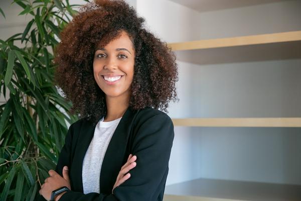 A imagem contém uma advogada bem sucedida sorrindo, pois está em dia com o desenvolvimento de sua carreira.