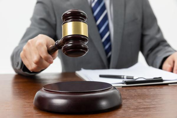 A imagem contém um juiz batendo o malhete.